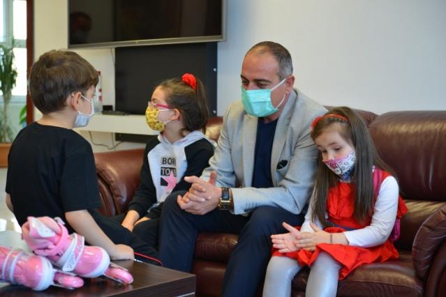 """Harçlığını bağışlayan çocuklara Başkan Sertaslan'dan sürpriz hediye Gemlik Belediye Başkanı Mehmet Uğur Sertaslan'ın öncülüğünde Cumhur ve Millet İttifakı partileri, Sivil Toplum Kuruluşları, Esnaf Odası, yerel basın ile Gemlik'teki yardımseverler iki gün boyunca ortak canlı yayında buluşarak Gemlik esnafının fatura borcu için 700.000 liralık taahhüt toplamıştı. Düzenlenen canlı yayına Gemlik'ten, Türkiye geneli ve dünyanın dört bir yanından adeta Gemlik esnafına destek yağmıştı. Beş yaşındaki Asya Erdem kumbarasını, 7 yaşındaki Mesut Karataş ve 9 yaşındaki Işıl Yaraş biriktirdiği harçlığını, 11 yaşındaki Kerem Aktay ise bisiklet almak için biriktirdiği miktarı esnafa bağışlamış ve programda duygusal anlar yaşanmasına sebep olmuşlardı. Gemlik Belediye Başkanı Mehmet Uğur Sertaslan ise bu duyarlı miniklere bisiklet hediye ederek onlara teşekkür etti. Çocukları birlikte makamında ağırlayan ve ailelerine teşekkür eden Gemlik Belediye Başkanı Mehmet Uğur Sertaslan, """"Çok kıymetli bizim için böyle bir sorumluluğun altına girip, bunu fark etmiş olmanız. Bizim için çok kıymetli size küçük bir hediyem var"""" dedi ve çocuklara hediyelerini armağan etti."""